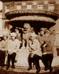 Students of the Girls School at the beginning of the 20th century sitting on the base of a large, stone statue in the gardens at Bentley Priory