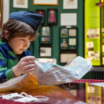 School student exploring a map, wearing a RAF cap from the Museum's handling collection